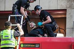 London, UK. 17th April 2019. Climate change activists from Extinction Rebellion are removed by police officers from a DLR train at Canary Wharf station after having used glue to secure themselves on the third day of International Rebellion activities to call on the British government to take urgent action to combat climate change.