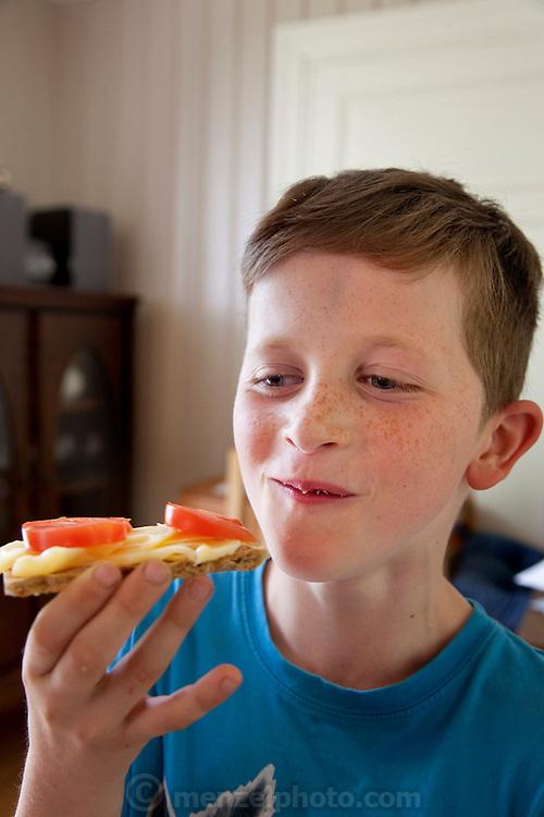 The Glad Ostensen family in Gjerdrum, Norway. Amund, 8, eats a sandwich in their farmhouse kitchen. Model-Released.