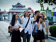 """11 SEPTEMBER 2017 - BANGKOK, THAILAND: Thai university students photograph the main entrance to Wat Arun. Renovations are nearly finished at Wat Arun on the Thonburi side of the Chao Phraya River in Bangkok. Wat Arun is famous for its Khmer style main """"prang"""" (chedi). It was originally built in the Ayutthaya Period and rebuilt to its current form in the time of Rama II.     PHOTO BY JACK KURTZ"""