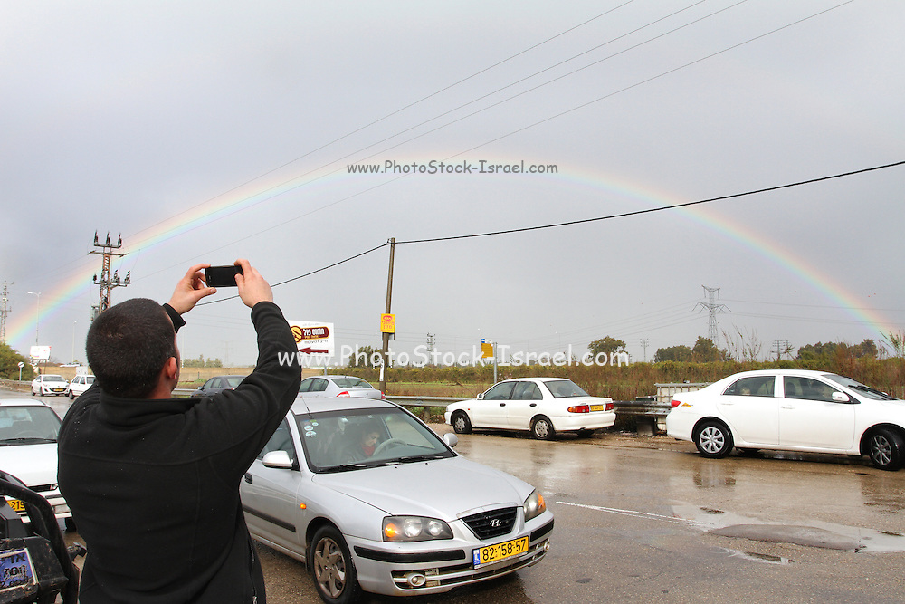 Cars pull over while the drivers look and photograph a full arc rainbow. Photographed in Israel