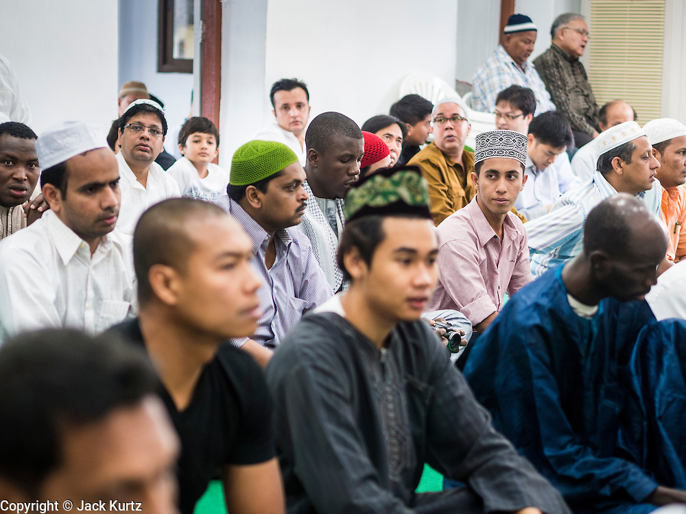 "08 AUGUST 2013 - BANGKOK, THAILAND: Men attend Eid al-Fitr services in a prayer room at Haroon Mosque in Bangkok. Eid al-Fitr is the ""festival of breaking of the fast,"" it's also called the Lesser Eid. It's an important religious holiday celebrated by Muslims worldwide that marks the end of Ramadan, the Islamic holy month of fasting. The religious Eid is a single day and Muslims are not permitted to fast that day. The holiday celebrates the conclusion of the 29 or 30 days of dawn-to-sunset fasting during the entire month of Ramadan. This is a day when Muslims around the world show a common goal of unity. The date for the start of any lunar Hijri month varies based on the observation of new moon by local religious authorities, so the exact day of celebration varies by locality.      PHOTO BY JACK KURTZ"