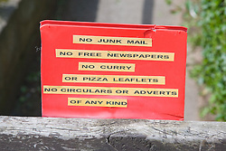 Sign outside house requesting the no junk mail is delivered; each year 78;000 tonnes of junk mail is generated and for each tonne of junk mail produced 17 trees; 7;000 gallons of water and 390 gallons of oil are used,