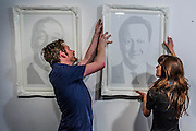 Srew fixings come of the wall while trying to hang David Cameron. Natalie Bennett, leader of the Green Party, unveils portraits of the five main UK party leaders, hand-written from Twitter opinions by artist Annemarie Wright. The portraits are of David Cameron, Ed Miliband, Nick Clegg, Nigel Farage and Natalie Bennett, who is the local Green Party candidate for Holborn and St Pancras. Each portrait takes her 30-40 hours to create, using varying thickness of pens. Woolff Gallery, Charlotte Street, London.