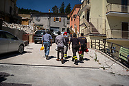 Fire fighters accompaining a family to save some itams in their unstable house. No one il allowded to enter the village of Castelluccio