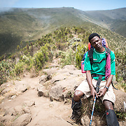A guide sits on a rock in the heath zone on Mt Kilimanjaro's Lemosho Trail at about 10,000 feet.