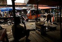 Man smoking in a street scene in a market, Jakarta, Indonesia.<br /> Homme fume dans une scène de rue du marché, Djakarta, Indonésie. 2009