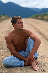 Man looking off with a thoughtful gaze on a dirt road in New Mexico
