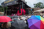 Umbrellas popped up in the audience at Celebrate Brooklyn as a light rain fell from time to time. Singer Jason Walker is on stage.
