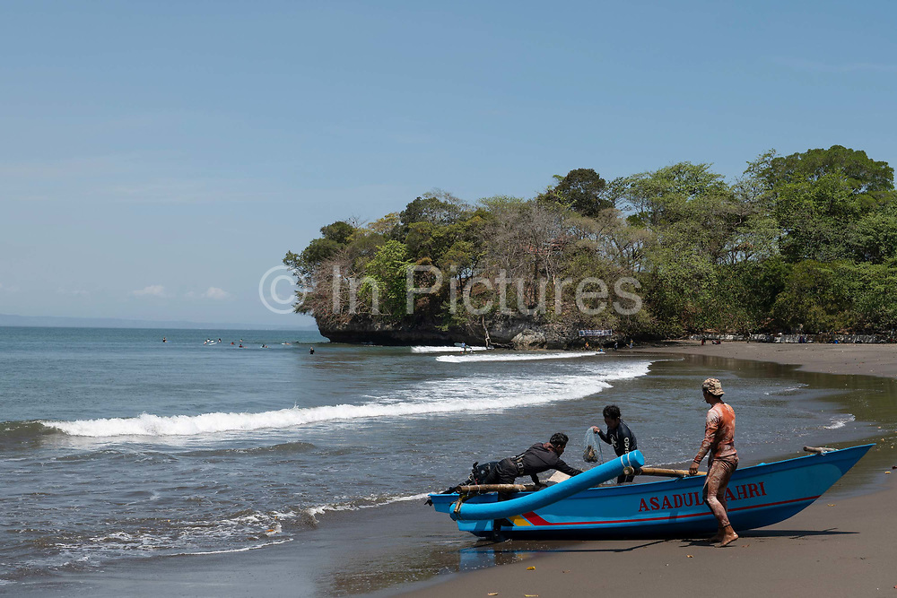 A traditional wooden fishing boat returns to the shore at Batu Karas on the 31st October 2019 in Java in Indonesia.