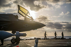 180922-M-PK127-1001<br /> GULF OF ADEN (Sept. 22, 2018) A Marine Corps F-35B Lightning II sits on the flight deck of the Wasp-class amphibious assault ship USS Essex (LHD 2) while Marines with Marine Fighter Attack Squadron 211, 13th Marine Expeditionary Unit (MEU), prepare for flight operations. The Essex Amphibious Ready Group and 13th MEU are the first U.S. Navy/Marine Corps team to deploy to the U.S. 5th Fleet area of operations with the transformational warfighting capabilities of the F-35B Lightning II, making it a more lethal, flexible and persistent force, leading to a more stable region for our partner nations (U.S. Marine Corps photo by Cpl. Francisco J. Diaz Jr./Released)