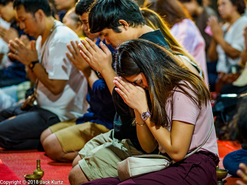 """01 MARCH 2018 - BANGKOK, THAILAND:    People pray as they're sprinkled with blessed water during Makha Bucha Day ceremonies at Wat Pathum Wanaram in central Bangkok. Many people go to temples to perform merit-making activities on Makha Bucha Day, which marks four important events in Buddhism: 1,250 disciples came to see the Buddha without being summoned, all of them were Arhantas, or Enlightened Ones, and all were ordained by the Buddha himself. The Buddha gave those Arhantas the principles of Buddhism. In Thailand, this teaching has been dubbed the """"Heart of Buddhism.""""    PHOTO BY JACK KURTZ"""