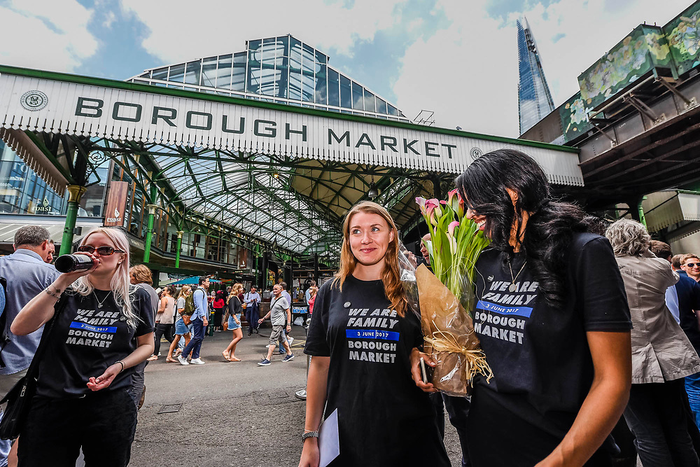 A group with We Are Family' t-shirts bring flowers for the staff of Black and Blue who sheltered them during the attack - Stoney street is soon thronging with lunchtime eaters and drinkers. The market reopening is signified by the ringing of the bell and is attended by Mayor Sadiq Khan. Tourists and locals soon flood back to bring the area back to life.