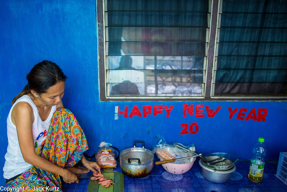 """11 JANUARY 2013 - BANGKOK, THAILAND:  A woman makes food she sells from her home in the Ban Krua neighborhood in Bangkok. The Ban Krua neighborhood of Bangkok is the oldest Muslim community in Bangkok. Ban Krua was originally settled by Cham Muslims from Cambodia and Vietnam who fought on the side of the Thai King Rama I. They were given a royal grant of land east of what was then the Thai capitol at the end of the 18th century in return for their military service. The Cham Muslims were originally weavers and what is known as """"Thai Silk"""" was developed by the people in Ban Krua. Several families in the neighborhood still weave in their homes.                  PHOTO BY JACK KURTZ"""