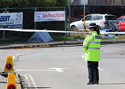 © Licensed to London News Pictures. 23/08/2015. Shoreham, UK.  A police officer guardian what is believed to be a tent covering a dead body at the scene (left, silver tent). Emergency services at the scene where a Hawker Hunter fighter jet crashed in to cars on the A27 road in front of thousands of spectators at the Shoreham Airshow in West Sussex with 7 people confirmed dead. Today August 23rd 2015. Photo credit : Hugo Michiels/LNP