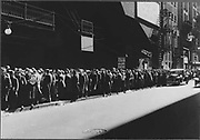 America in the Great Depression, 1930s. Men queue for a five-cent meal. Those on left of sign will get their meal, those further up the queue must hope for a generous passerby.