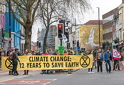 © Licensed to London News Pictures. 16/02/2019. Bristol, UK. Extinction Rebellion Bristol hold a street party and road blockade in Stokes Croft, forcing traffic to divert. Today's action is to help set the stage for Extinction Rebellion's International Rebellion starting April where thousands will occupy the streets of London. Extinction Rebellion say the Bristol street party is a family friendly event to reclaim the streets of the city, and that they are in open, peaceful rebellion against the UK Government and will not accept the mere declaration of a climate emergency; concrete action must follow. Extinction Rebellion say Bristol airport must not expand and that doing so is a foolish and dangerous decision. There are a variety of spoken word, musical, and circus performers, and it will be an alcohol and drug free space. Photo credit: Simon Chapman/LNP