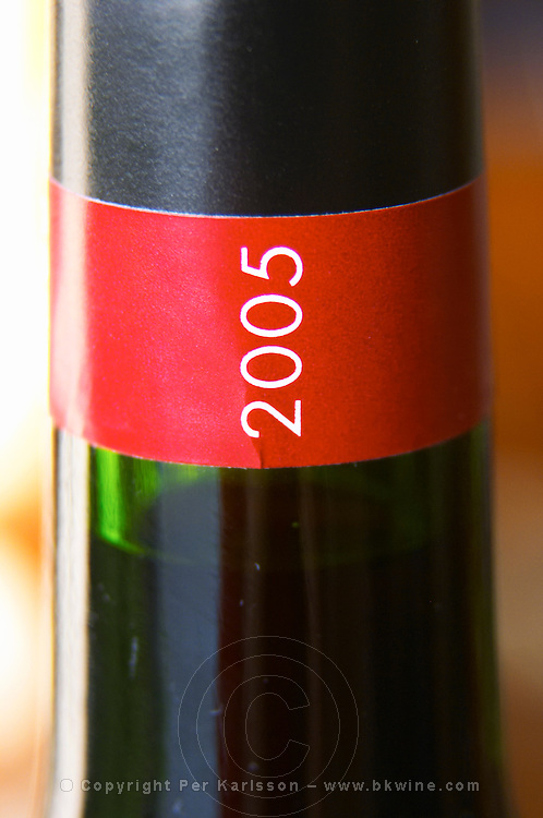 Detail of red and black neck label with the vintage year 2005 in white letters vertically Madiran France