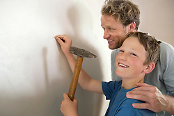 Smiling father son working together hammer wall