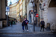 A young couple with face masks waiting at a traffic light close to Charles Bridge. On March 1st, 2021 the state of emergency in the Czech Republic was reinstalled because of fast increasing numbers in infections. The lockdown was reinstated and the restriction of the free movement of people has taken effect. Currently, the country remains at the highest stage of the anti-epidemiological system and the newly imposed restriction will last at least three weeks to curb the epidemic.