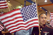 """04 JULY 2009 -- PHOENIX, AZ:  Corporal TUNG NGUYEN, US Marine Corps, originally from Vietnam, waves an American flag after being naturalized a US citizen at a naturalization ceremony in Phoenix, AZ, July 4. U.S. Citizenship and Immigration Services and South Mountain Community College in Phoenix, AZ, hosted the 21st annual """"Fiesta of Independence"""" Saturday, July 4. More than 180 people from 58 countries took the US Oath of Citizenship and became naturalized US citizens. The ceremony was one of dozens of similar ceremonies held across the US this week. USCIS said more than 6,000 people were naturalized US citizens during the week.  Photo by Jack Kurtz / ZUMA Press"""