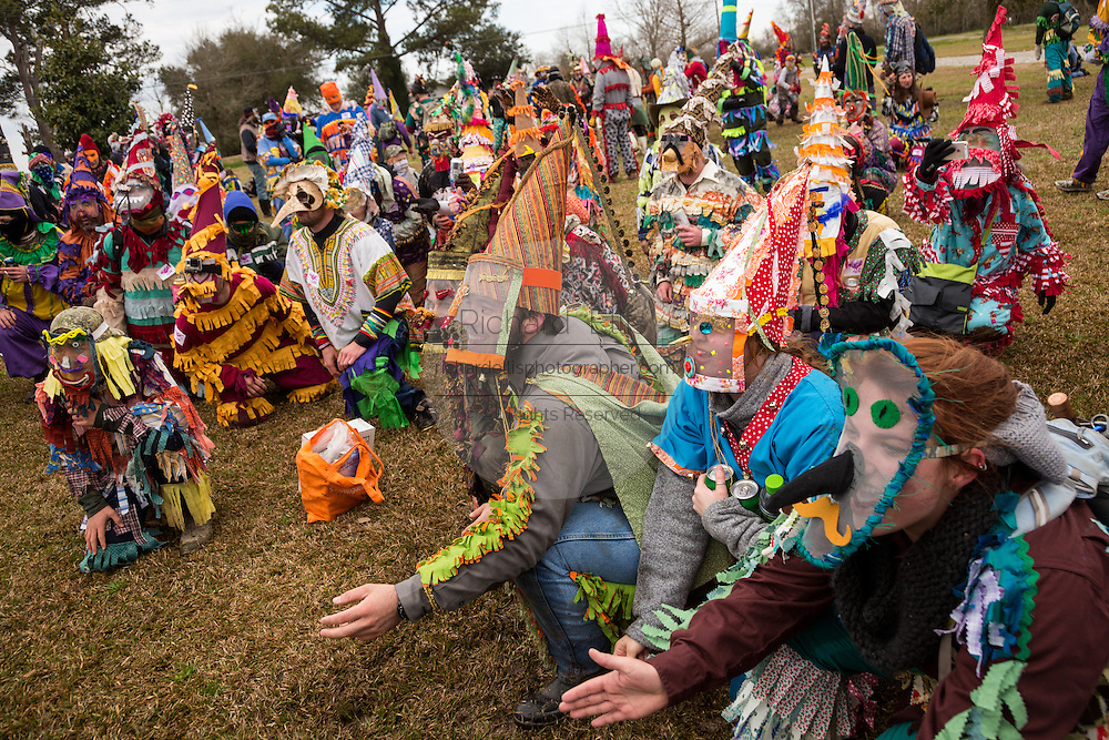 Costumed revelers beg for food donations from a home owner during the Faquetigue Courir de Mardi Gras chicken run on Fat Tuesday February 17, 2015 in Eunice, Louisiana. The traditional Cajun Mardi Gras involves costumed revelers competing to catch a live chicken as they move from house to house throughout the rural community.