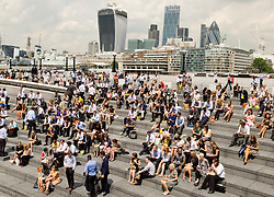 © Licensed to London News Pictures. 24/06/2014. London, UK. Office workers enjoying the hot weather in London at lunchtime today on the bank of the River Thames opposite the City of London. Photo credit : Vickie Flores/LNP