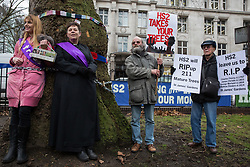 London, UK. 12th January, 2018. Anne Stevens, the vicar of St Pancras church, is chained to a tree with Jo Hurford outside Euston station as part of a campaign by local residents in protest against the planned felling of mature London Plane, Red Oak, Common Whitebeam, Common Lime and Wild Service trees in Euston Square Gardens to make way for temporary sites for construction vehicles and a displaced taxi rank as part of preparations for the HS2 rail line.