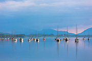 Yachts moored on Loch Creran, reflected on the sea loch at sunset on west coast of Scotland, near Creagan in Argyll and Bute region