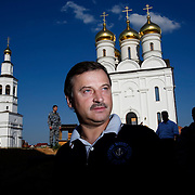 Russian billionaire Sergei Veremeenko poses in front of an Orthodox church he built in a village outside Moscow, Russia, surrounded by his armed bodyguards.