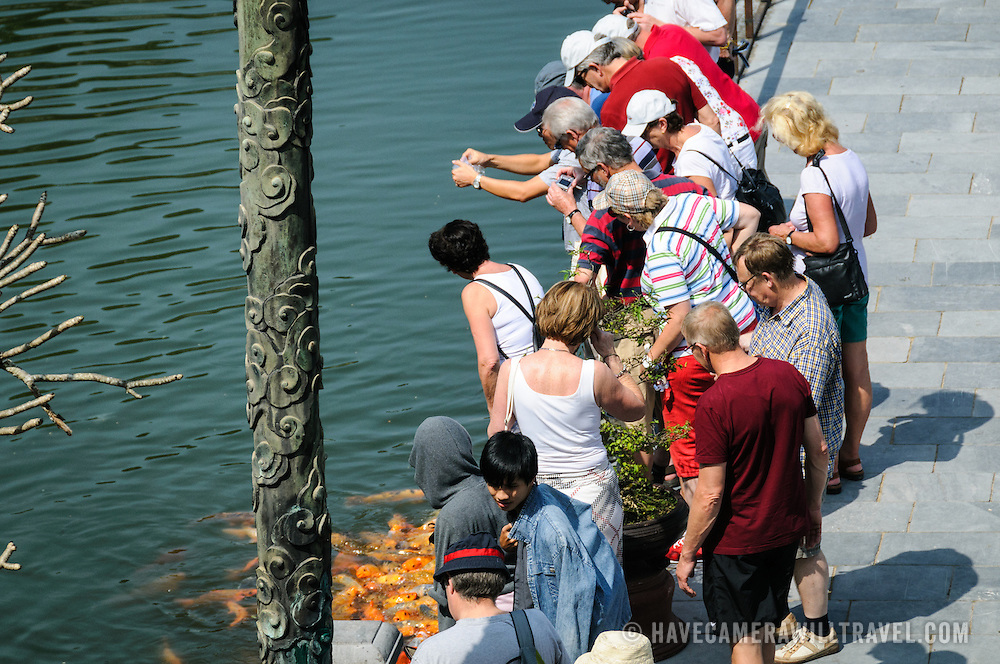 Tourists feed the carp at the Imperial City in Hue, Vietnam. A self-enclosed and fortified palace, the complex includes the Purple Forbidden City, which was the inner sanctum of the imperial household, as well as temples, courtyards, gardens, and other buildings. Much of the Imperial City was damaged or destroyed during the Vietnam War. It is now designated as a UNESCO World Heritage site.