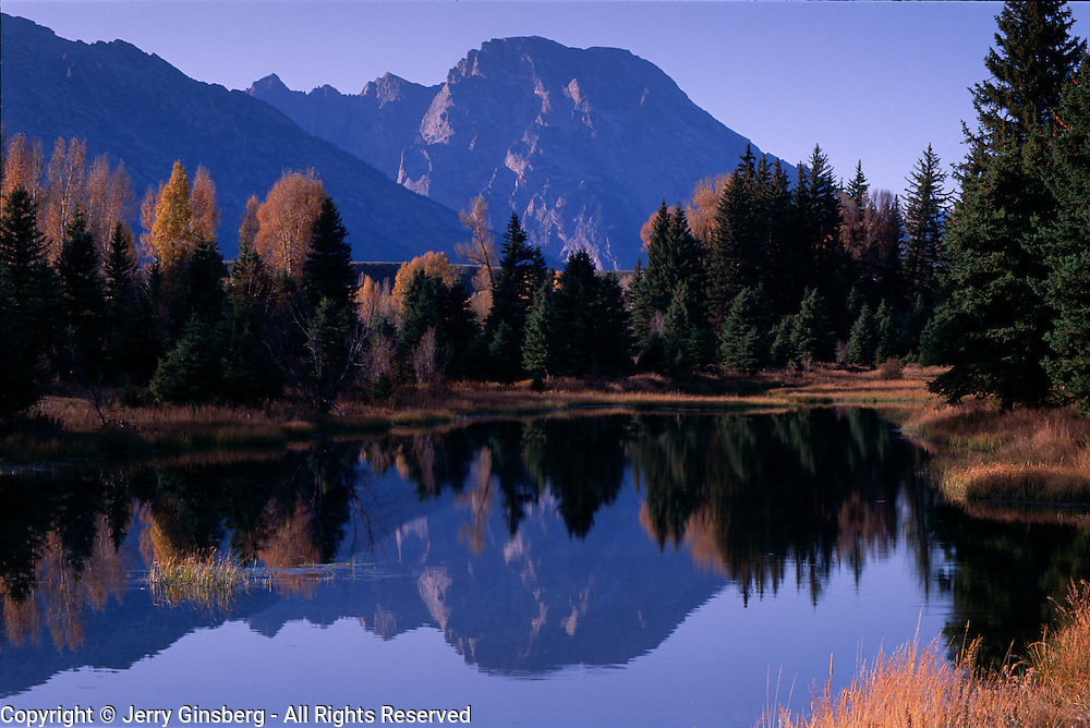GRand Tetons reflect in the Snake River in Grand Teton National Park, Wyoming.