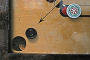 The corner pocket of a carom board during a game. Players have to strike the coins (Carrommen) into the pockets using the 'striker'.