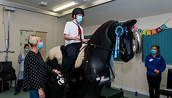 East Lothian, Scotland, UK, NHS Lothian & Muirfield Riding Therapy celebrate 10 years of Hippotherapy:Physiotherapist Heather Falconer  pioneered The Children's Therapeutic Riding Service providing therapeutic riding free of charge to children and adults with disabilities. The service was the first in Scotland. Children with mobility, balance, muscle tone and coordination problems benefit. Oreo, a mechanical horse, allows youngsters to receive fun physiotherapy. Charlie Kay, aged 13 years who has been a participant  since the beginning of the project, rides Oreo.<br /> Sally Anderson | EdinburghElitemedia.co.uk
