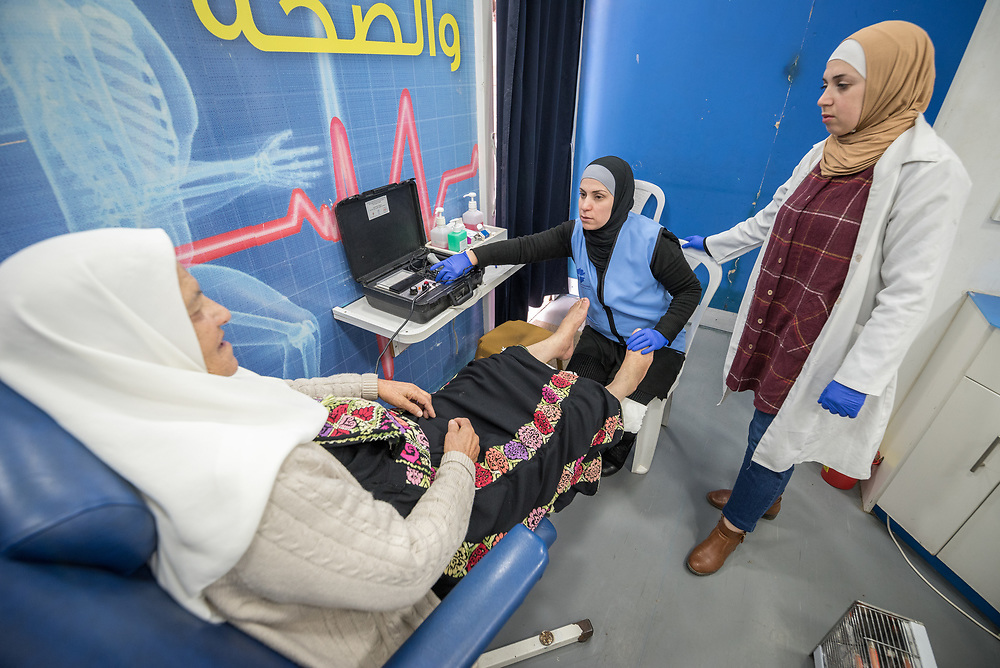 26 February 2020, Abu Dis, Palestine: Nurse Najwa Hawamdeh administers a foot exam as 87-year-old Diabetes patient Hamama Jaffal from Abu Dis visits the Augusta Victoria Hospital's Mobile Diabetes Clinic. Here, carrying out a vibration sensitivity test. In an effort to make Diabetes services more accessible to people in the West Bank, the Augusta Victoria Hospital offers a Mobile Diabetes Clinic, which moves around to various locations in the West Bank, offering screening and routine testing for Diabietes and the symptoms it causes.