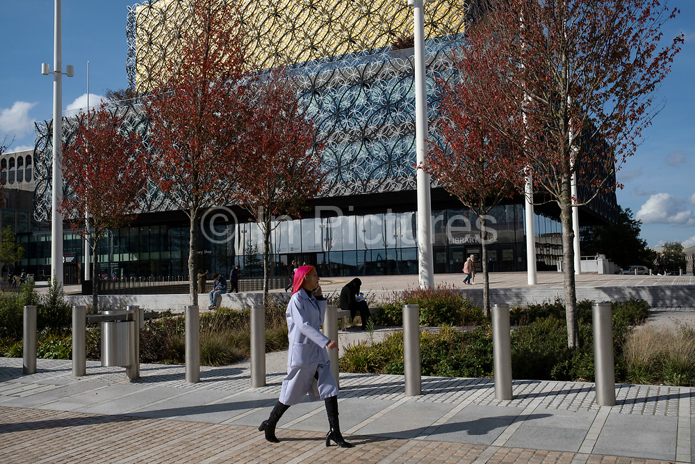 As numbers of Covid-19 cases in Birmingham have dramatically risen in the past weeks, increased lockdown measures have been announced for Birmingham and other areas of the West Midlands, people enjoy the sunshine in Centenary Square in front of the Library of Birmingham while the city centre is still very quiet on 29th September 2020 in Birmingham, United Kingdom. With the rule of six also being implemented the Birmingham area has now be escalated to an area of national intervention, with a ban on people socialising with people outside their own household, unless they are from the same support bubble.