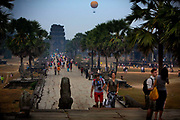 Crowds visiting Angkor Wat with Angkor Wat Balloon in distance. <br /> The balloon is 1k west of the Angkor Wat.The German made helium balloon is attached to a rope and ascends approximately 200 metres, floats for a while and then descends. It isn't actually a tour and it only lasts about 10 minutes but it is enough to get some great pictures of Angkor Wat on a clear day. The balloon flies approximately 30 times a day from sunrise to sundown and can carry up to 30 passengers.