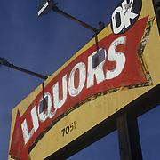 "Vintage, colorful painted sign reading ""Liquors, OK"" near Watsonville, CA. Looking upward against dark blue sky."