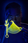 Young man with moving glowing chain.Black light