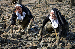 © London News Pictures. 05/05/2013. Maldon, UK. Competitors dressed as nuns take part in the Maldon Mud Race in Maldon, Essex on May 05, 2013. The race originated in 1973 and involves competitors racing around a course on the mudbanks of the river Blackwater at low tide. Photo credit: Ben Cawthra/LNP.