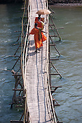 Bamboo bridge across the Nam Khan River, Luang Prabang, Laos. Monks crossing.