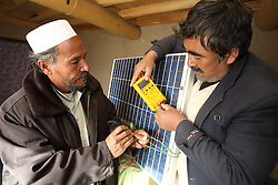 Mohammad Jan an NCA trained Master Barefoot Solar Engineer training Alijan  who is also a Barefoot Solar Engineer working on preparing solar panels at a workshop in his home in Palaj Village, Shahrestan, Daikundi Province, Afghanistan.