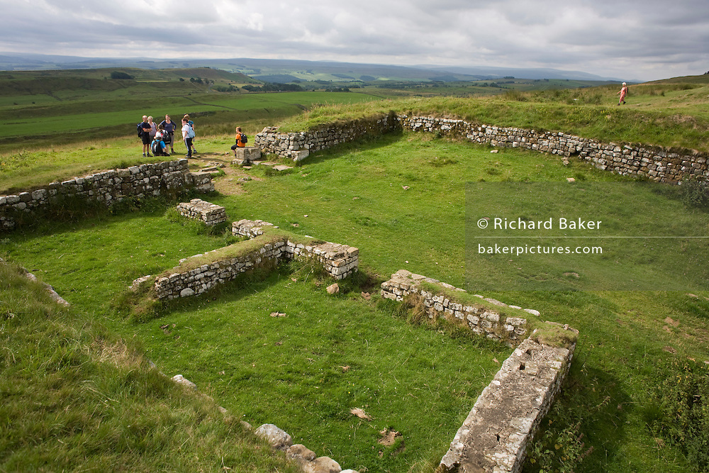 Walkers explore Milecastle 39 on Roman Hadrian's Wall, once the northern frontier of Rome's empire from Barbarian tribes.