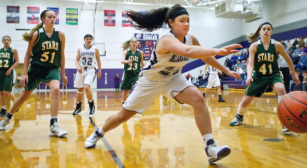 Wood River's Julia Rojas attempts to save a ball headed out of bounds in the third period of Friday's Lou-Platte Conference Tournament game at Wood River High School. Also in the play are Kearney Catholic's Megan Anderson (51) and Maddie Squiers (41). Kearney Catholic won 73-32. (Independent/Matt Dixon)