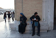 A couple of people watch for tourists near the Vatican. What are they up to exactly?