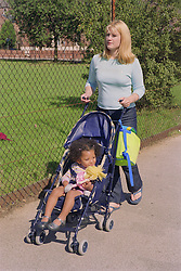 Young mother pushing daughter in pushchair along pavement next to park,