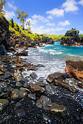 """Black sand beach in Waianapanapa State Park, Maui, Hawaii<br /> .....<br /> The island of Maui is the second-largest of the Hawaiian Islands and is the 17th largest island in the United States. Maui is part of the State of Hawaii and is the largest of Maui County's four islands, bigger than Molokaʻi, Lānaʻi, and unpopulated Kahoʻolawe. Native Hawaiian tradition gives the origin of the island's name in the legend of Hawaiʻiloa, the navigator credited with discovery of the Hawaiian Islands. According to that legend, Hawaiʻiloa named the island of Maui after his son, who in turn was named for the demigod Māui. The earlier name of Maui was ʻIhikapalaumaewa. The Island of Maui is also called the """"Valley Isle"""" for the large isthmus between its northwestern and southeastern volcanoes and the numerous large valleys carved into both mountains."""