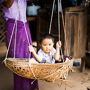 A small child swings in a woven basket in Minnanthu Village in Bagan, Myanmar. Set amidst the archeological ruins of the Plain of Bagan, the tiny Minnanthu Village retains the traditional way of life.