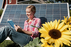 Young woman reading book leaning on solar panel