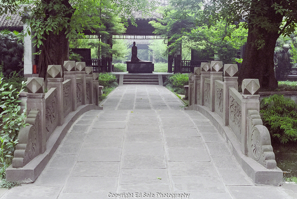 A statue of the Chinese Tang Dynasty poet Dufu rests at the far end of a stone bridge and walkway at his residence in Chengdu, China