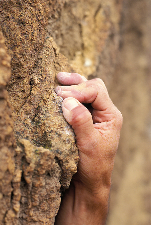 A rock climber gripping on a hold on a climbing route at Smith Rock State Park, Oregon, USA